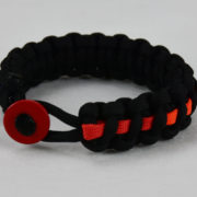 black lgbtq support paracord bracelet with rainbow line and red button fastener in the front
