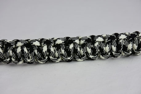 black and white camouflage paracord bracelet across the center of a white background
