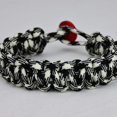 black and white camouflage paracord bracelet with red button, picture of a black and white camouflage paracord bracelet with red button fastener in the back on a white background
