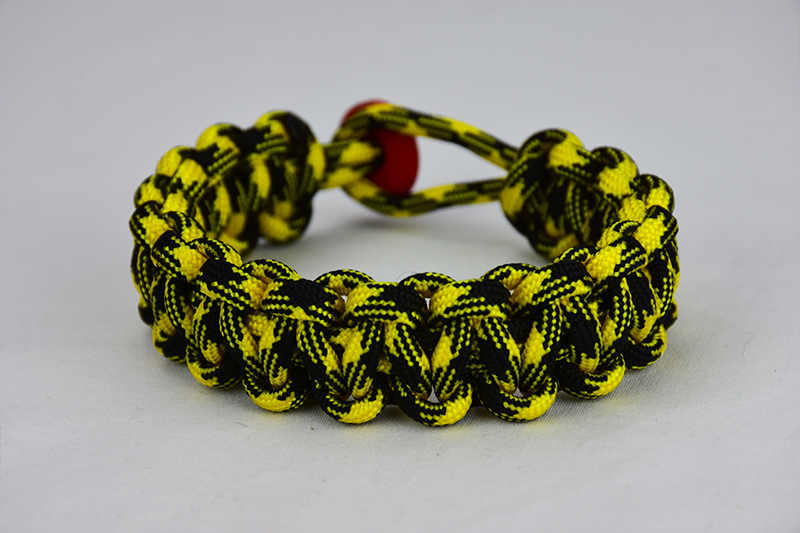 black and yellow camouflage paracord bracelet with red button in the back, picture of a black and yellow camouflage paracord bracelet with red button fastener in the back on a white background