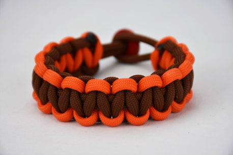 brown orange and brown paracord bracelet unity band with red button in back, picture of a brown orange and brown paracord bracelet unity band with red button fastener in the back on a white background