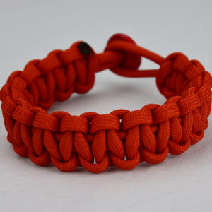burnt orange paracord bracelet unity band red button back, picture of a burnt orange paracord bracelet unity band with red button fastener in the back on a white background