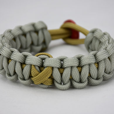 gold and grey pediatric cancer support paracord bracelet unity band, picture of a gold and grey paracord bracelet with a gold ribbon in the center and red button in the back