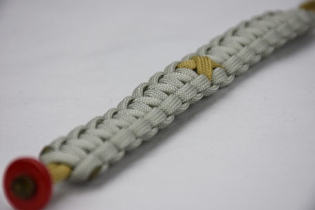 gold and grey pediatric cancer support paracord bracelet with gold ribbon and red button in the front corner