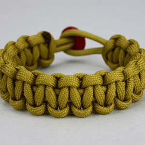 gold paracord bracelet unity band with red button, picture of a gold paracord bracelet unity band with a red button fastener in the back on a white background