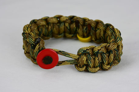 multicam camouflage military support paracord bracelet with red button front, picture of a multicam camouflage military support paracord bracelet with red button and yellow ribbon on a white background