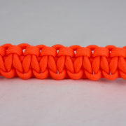 neon orange paracord bracelet across the center of a white background