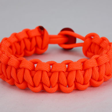 neon orange paracord bracelet unity band with red button, picture of a neon orange paracord bracelet unity band with red button fastener in the back on a white background