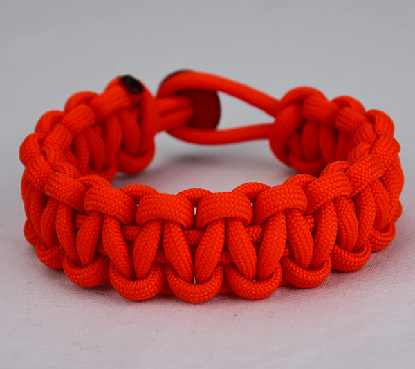 orange paracord bracelet unity band, picture of a orange paracord bracelet with a red button in the back, orange unity band paracord bracelet