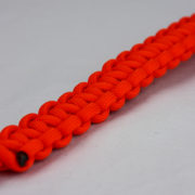 orange paracord bracelet unity band with red button in the bottom corner, orange paracord bracelet unity band with red button