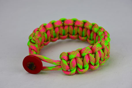 pink and neon green camouflage paracord bracelet unity band with red button in the front, picture of a pink and neon green paracord bracelet unity band with red button fastener in the front on a white background