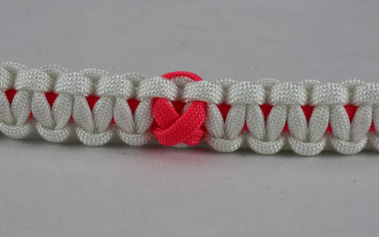 pink and white breast cancer support paracord bracelet with pink ribbon in the center