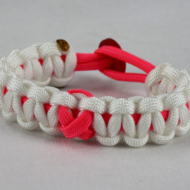 pink and white breast cancer support paracord bracelet with red button back and pink ribbon