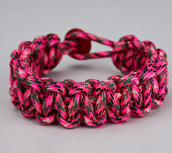 pink camouflage paracord bracelet unity band w red button in back, picture of a pink paracord bracelet unity band with red button fastener in the back
