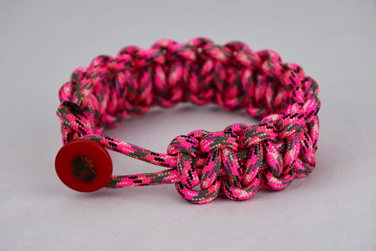 pink camouflage paracord bracelet unity band with red button on front, picture of a pink camouflage paracord bracelet with red button fastener on the front and a white background