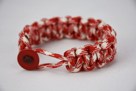red and white camouflage paracord bracelet with red button in front, picture of a red and white camouflage paracord bracelet unity band with red button fastener in the front on a white background