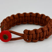 rust paracord bracelet with red button in the front, picture of a rust paracord bracelet unity band with red button fastener on a white background