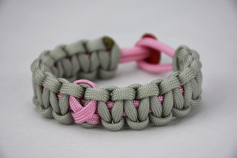 soft pink and grey breast cancer support paracord bracelet with pink ribbon and red button, picture of a unity band soft pink and grey breast cancer support paracord bracelet with a pink ribbon in the center and a red button fastener