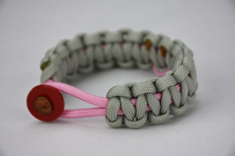 soft pink and grey breast cancer support paracord bracelet with a pink ribbon and red button, picture of a soft pink and grey breast cancer support paracord bracelet unity band with a red button in the front and pink ribbon in the back