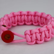 soft pink paracord bracelet unity band with red button in front, picture of a soft pink paracord bracelet unity band with red button fastener in the front on a white background