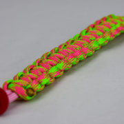 soft pink pink and neon green camouflage paracord bracelet unity band with red button in the corner, picture of a soft pink pink and neon green camouflage paracord bracelet unity band with red button fastener in the corner on a white background