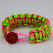 soft pink pink and neon green camouflage paracord bracelet unity band with red button in the front, picture of a soft pink pink and neon green paracord bracelet with red button fastener in the front on a white background