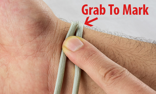 how to size a paracord bracelet, picture of a wrist with rope around it and an arrow pointing to where the rope meets itself and says grab to mark