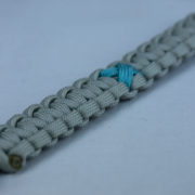 teal and grey ptsd support paracord bracelet with red button corner and teal ribbon