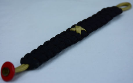 gold and black pediatric cancer support paracord bracelet with red button fastener in the corner and gold ribbon