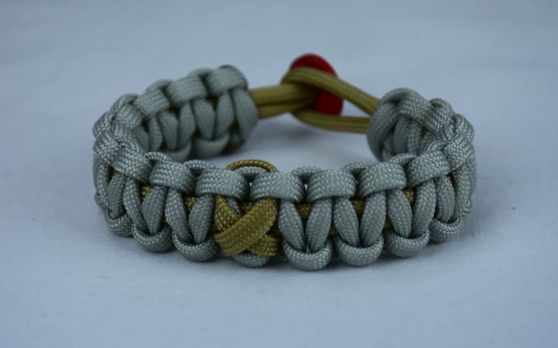 gold and grey pediatric support paracord bracelet with red button back and gold ribbon