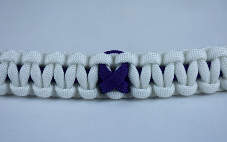 purple and white alzheimers support paracord bracelet with purple ribbon in the center of a white background