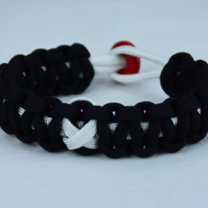 white and black multiple sclerosis support paracord bracelet with red button in back and white ribbon