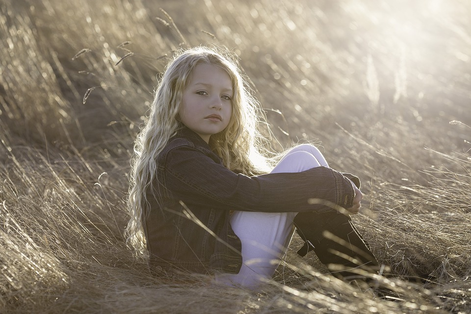 young kid sitting in a field looking somber